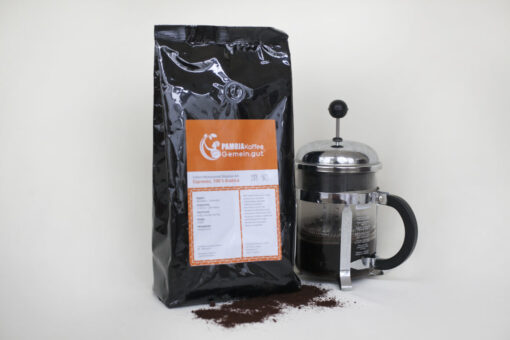 schwarze Tüte säurearmer Espresso Indian Monsooned Malabar AA davor dunkle Kaffeebohnen rechts Kaffeekanne