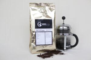 Kaffeebeutel mit Stempelkanne davor geröstete Kaffeebohnen