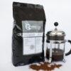 kilo espresso schwarzer alubeutel graues weisses Etikett Stempelkanne mit Kaffee drinnen und geröstete Bohnen vorne ausgebreitet