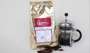 kilo kaffee goldener alubeutel rot-weisses Etikett stempelkanne mit Kaffee drinnen und geröstete Bohnen vorne ausgebreitet