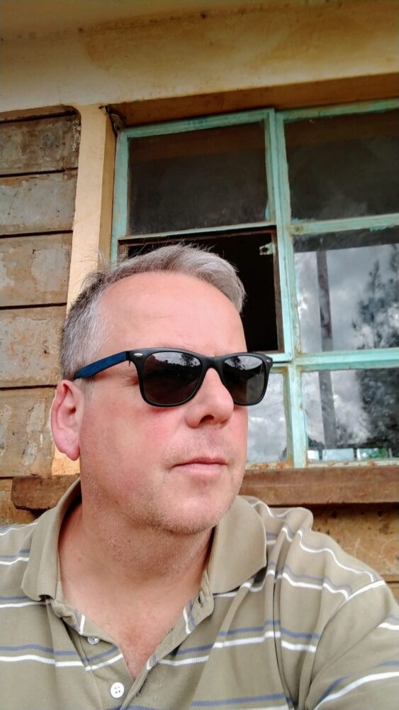 blonder mann im gestreiften Poloshirt mit Sonnenbrille Hintergrund Fenster Gitter Schule Kenia Shule