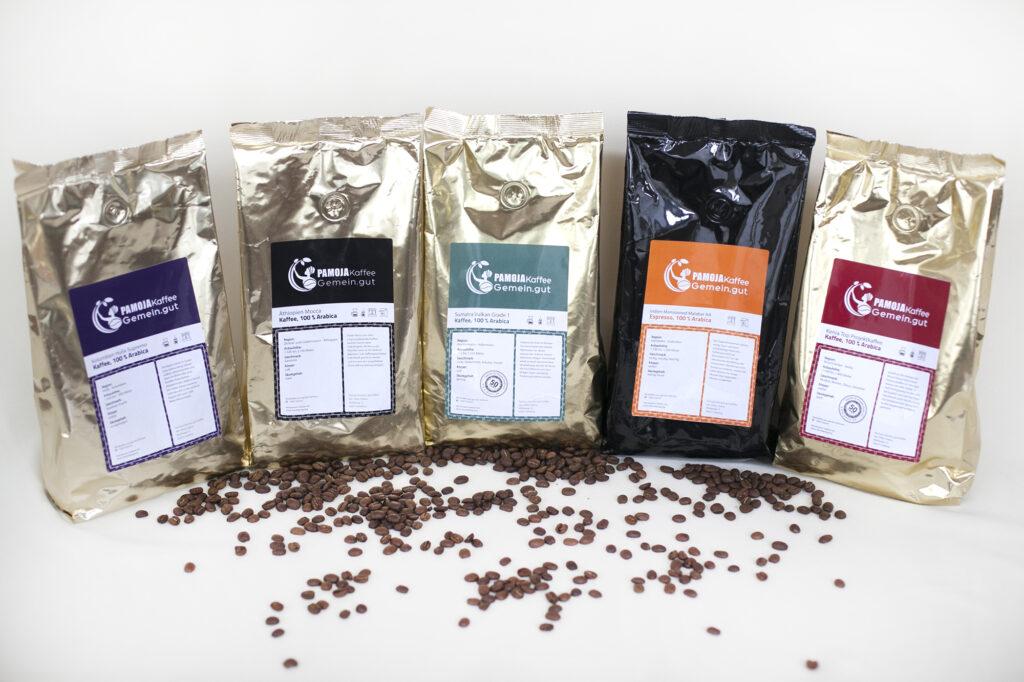 sortiment an alutueten pamojakaffee espresso drei kontinente arabica geröstete Bohnen liegen im Vordergrund auf hellem Hintergrund