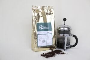 kilo kaffee goldener alubeutel grünes Etikett stempelkanne mit Kaffee drinnen und geröstete Bohnen vorne ausgebreitet