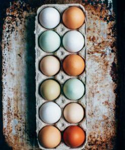 zwölf eier im karton auf rostigem blechtisch.