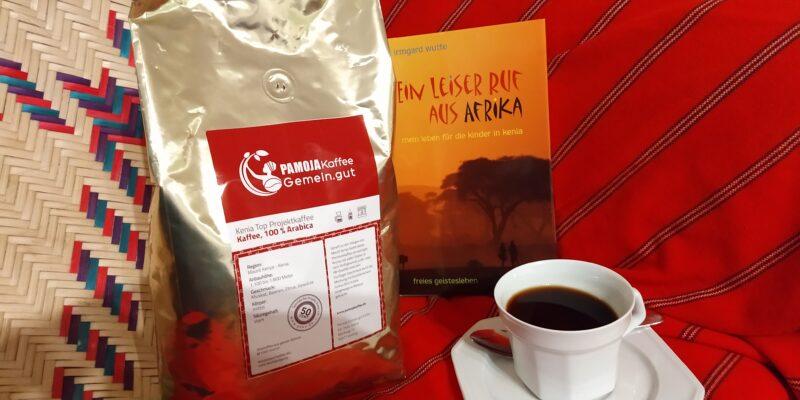 Geschenke unter 40 Euro Buch einer deutschen Lehrerin Kenia Tasse Kaffee goldenes Kaffeepäckchen Hintergrund Decke rot mit Streifen Bastkorb gemustert