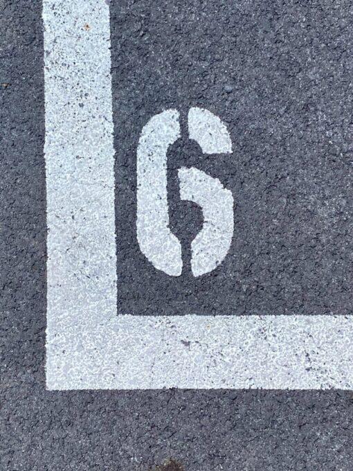 asphalt mit l-förmiger weißer linie mit der Zahl Sechs in weiß gemalt