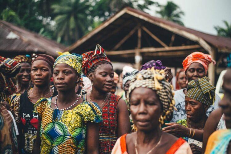 Dorf mit Frauen in Afrika butne kleider Schmuck Hintergrund Holzhaus