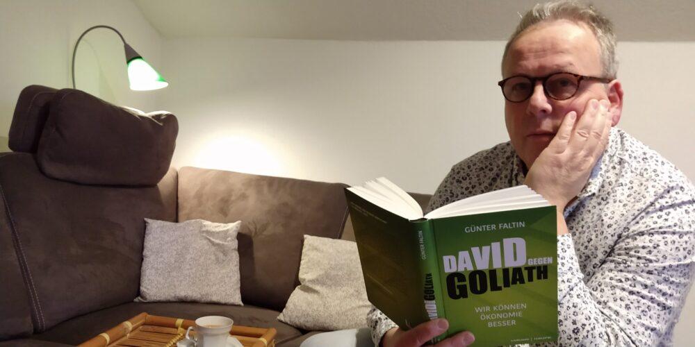 Mann mit Buch David gegen Goliath trinkt Kaffee