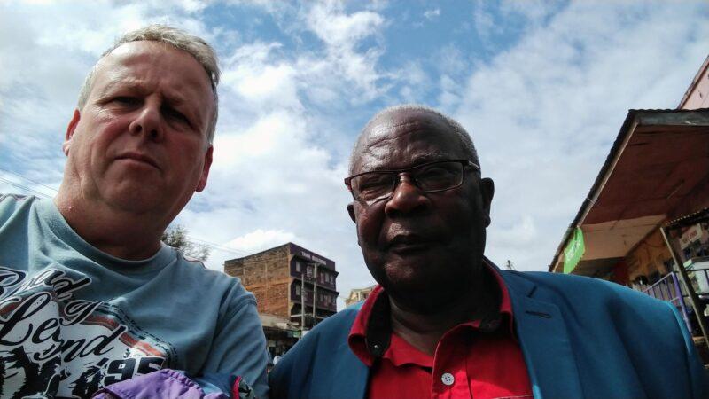 europäer im t-shirt mit afrikanischem mann im roten hemd und blauem jacket und brille