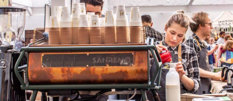 blonde Frau schaeumt Milch auf als Barista hinter italienischer Kaffeemaschine daneben Mann und macht richtig guten Kaffee und Espresso