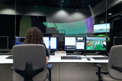 Frau sitzt am PC in einem Raum voller Computer und Monitore